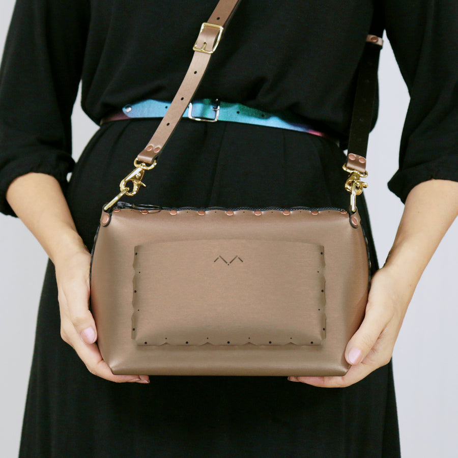 Model showcasing the outside pocket of mocha small crossbody bag