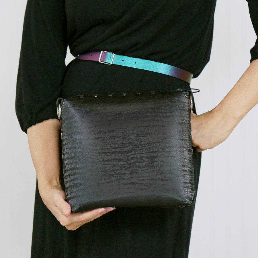 Model holding onyx medium crossbody bag