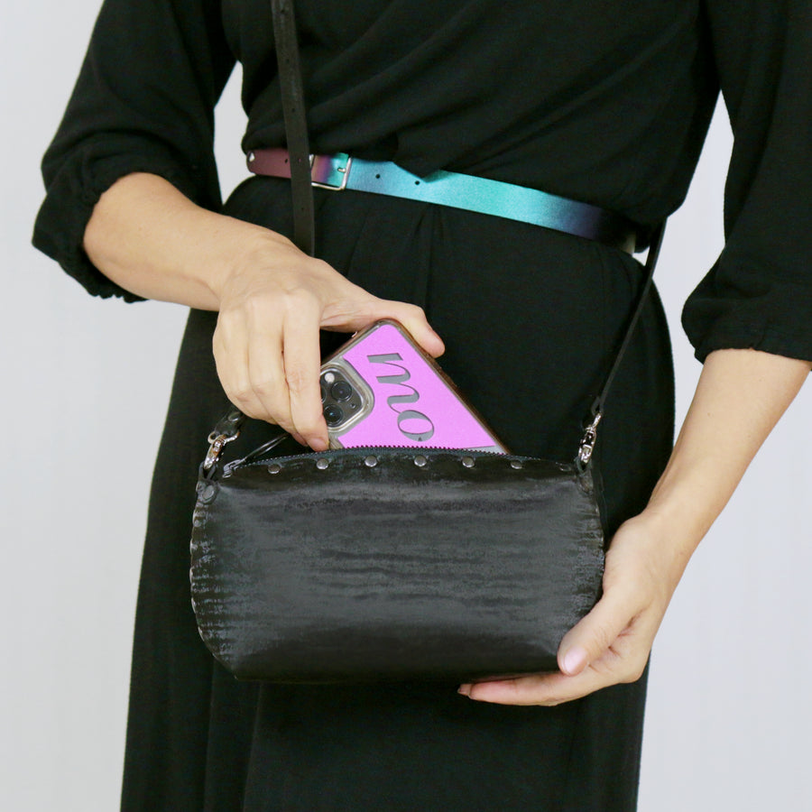 Model placing phone inside onyx mini bag