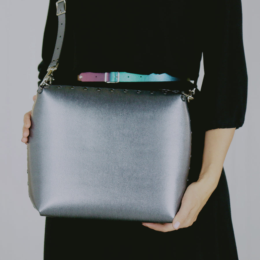 Model holding large pewter crossbody bag