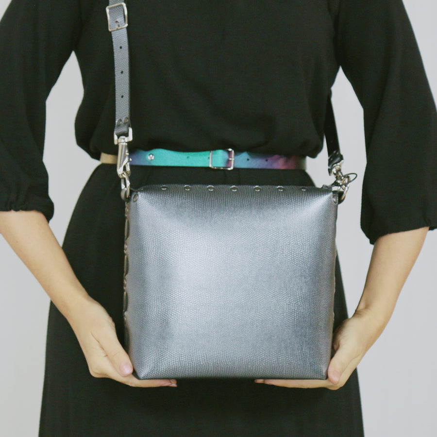 Model wearing pewter medium crossbody bag