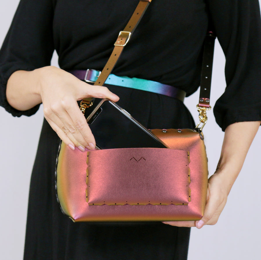 Model removing phone from outside pocket of ruby small crossbody bag