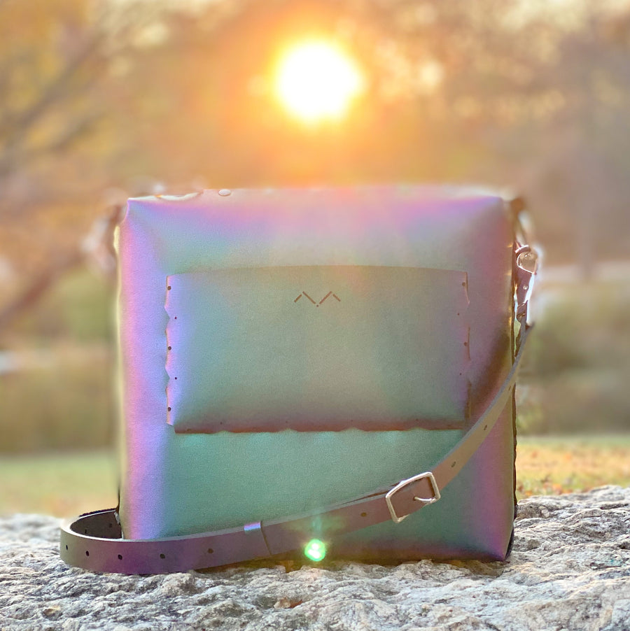 Chameleon medium crossbody body glowing majestically amongst the rays of a setting sun
