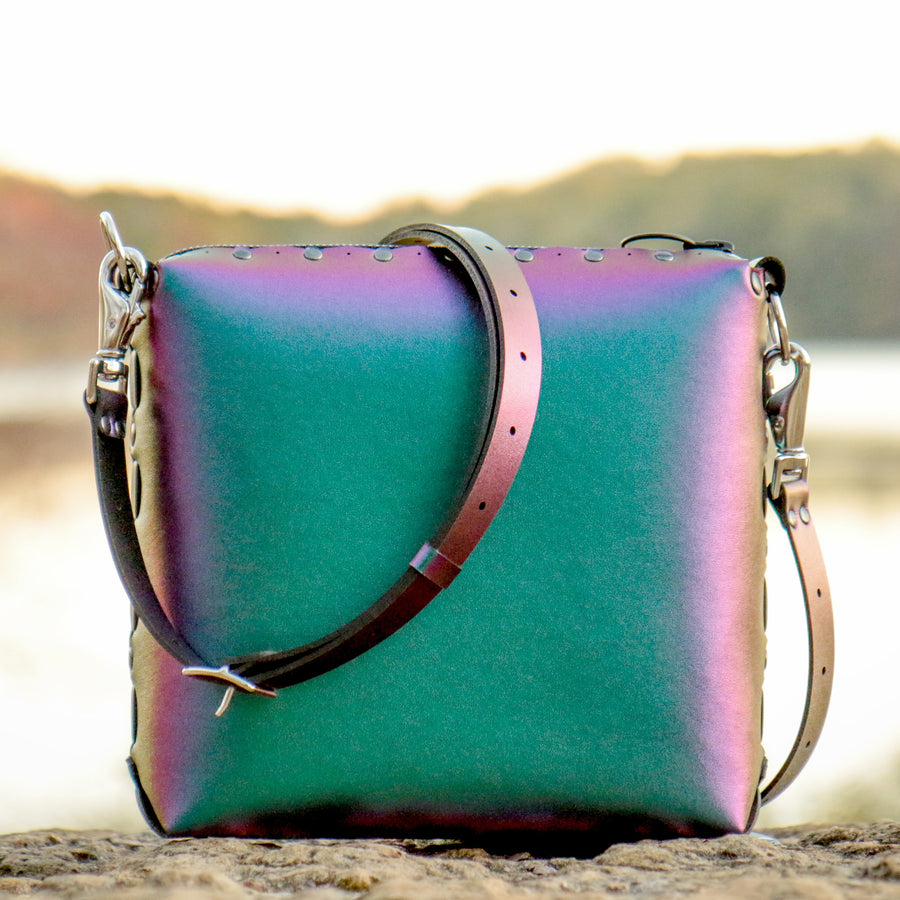Chameleon medium crossbody bag photographed lakeside at sunset