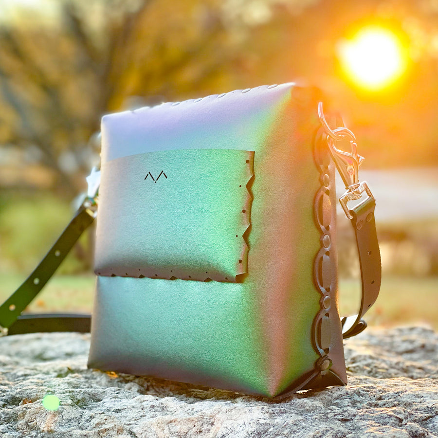 Emerald medium crossbody bag with iridescent glow during sunset