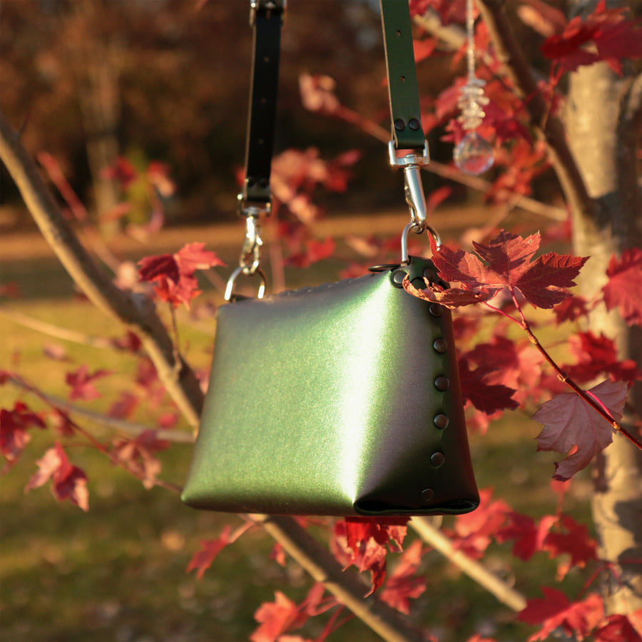 Emerald small crossbody bag glowing bright in autumn sunset