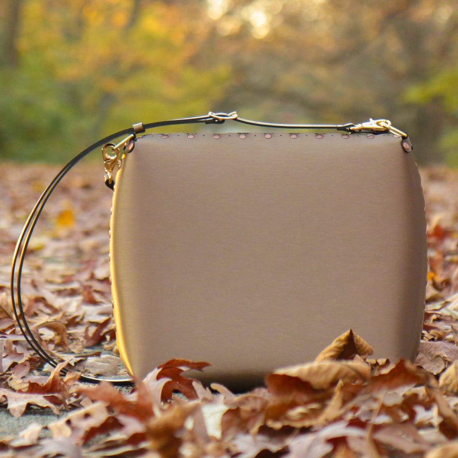 Large mocha crossbody bag in fall leaves during sunset