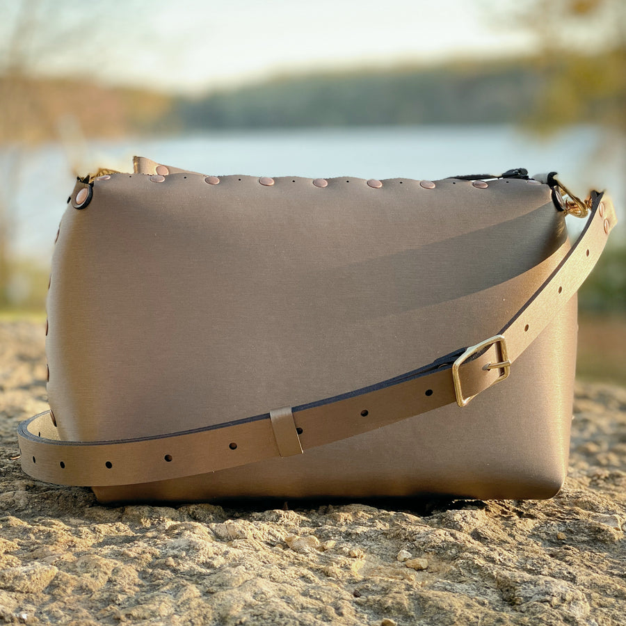 Mocha small crossbody bag shining brightly under setting sun