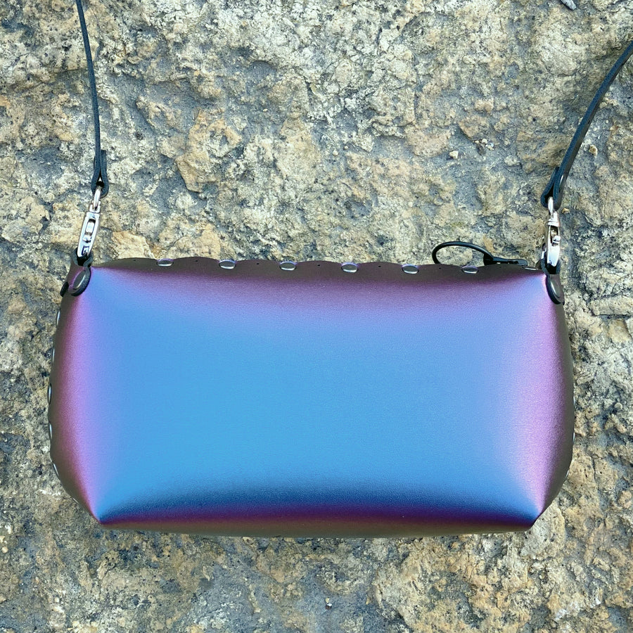 Peacock mini bag in front of stone wall with iridescent shine