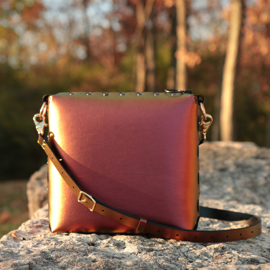 Ruby medium crossbody bag set amongt the rocks shimmering from the warm autumn sunset