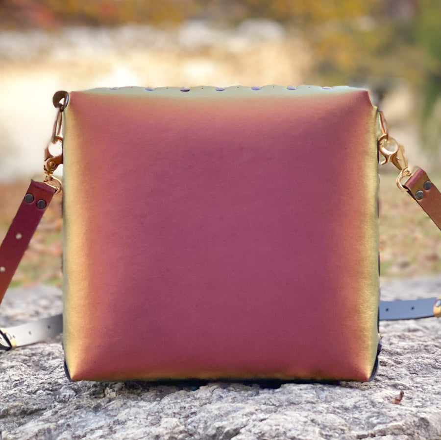 Ruby medium crossbody bag posed on a rock in a park in fall