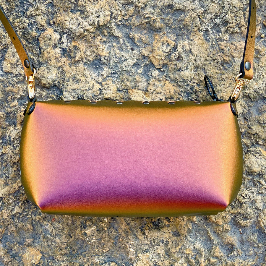 Ruby mini bag glowing with red iridescence in fall sunset