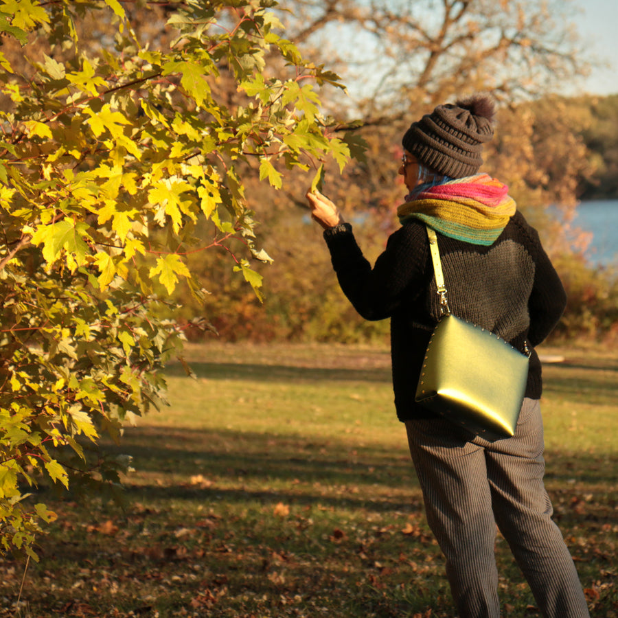 Women wearing large scarab crossbody bag during autumn sunset