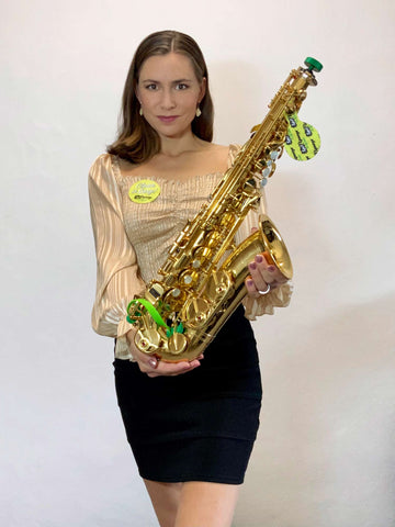 Czech sax player Katerina Palikova holding her alto saxophone with Key Leaves care products