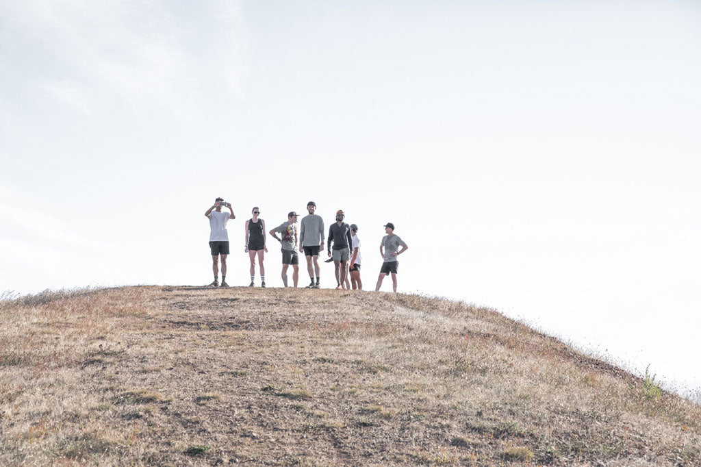 group of runners standing on top of hill