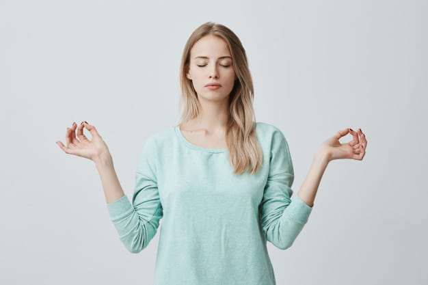 Restful peaceful blonde female feels relaxed, stands in lotus pose, tries to concentrate or to be focused, closes eyes, enjoys silence, tries to find balance. calm atmosphere and meditation Free Photo