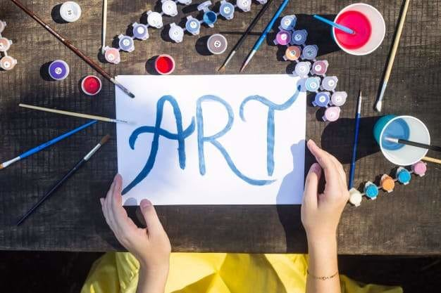 The word art is written in blue paint on a white sheet of paper among the brushes and paints for drawing. creativity and hobby concept Premium Photo