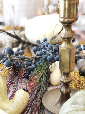 Brass candlesticks and blueberry sprigs on Thanksgiving tablescape