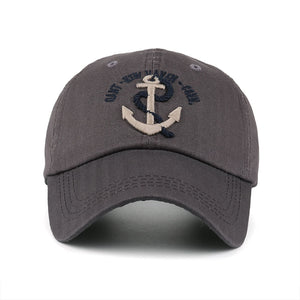dark gray mens baseball hat with tan anchor logo and blue font by anchor in waves