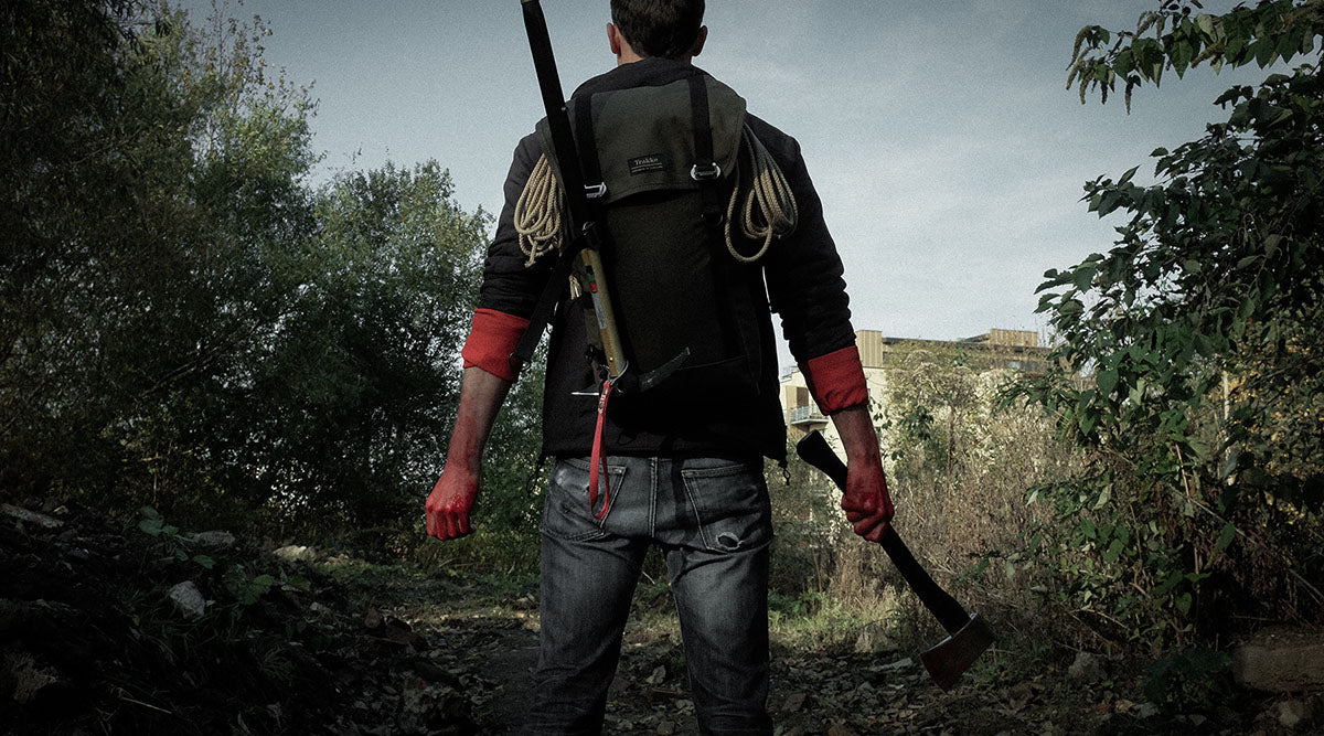 Man standing holding an axe wearing a Trakke bag, ready to fight zombies