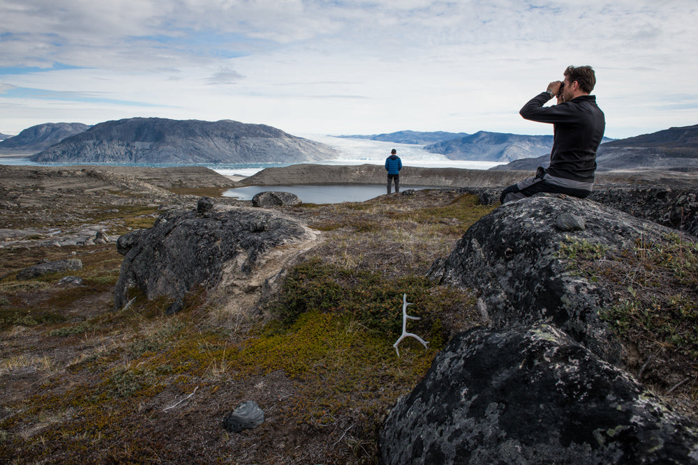A man with binoculars sits on a boulder and surveys the surrounding area in the wild in Greenland