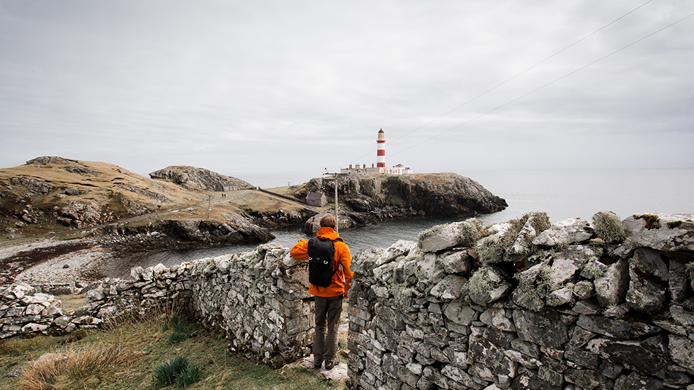 A man and his Trakke Bag - a black Assynt 28 - stands infront of Eilean Glas lighthouse in the Outer Hebrides Scotland
