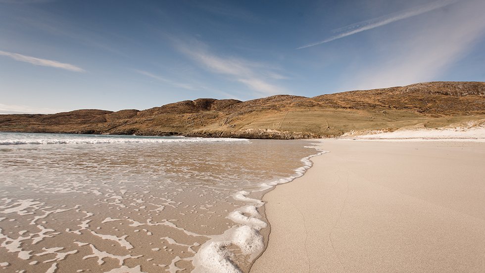 A picture showing the sand meeting the sea on west bay beach in the Outer Hebrides