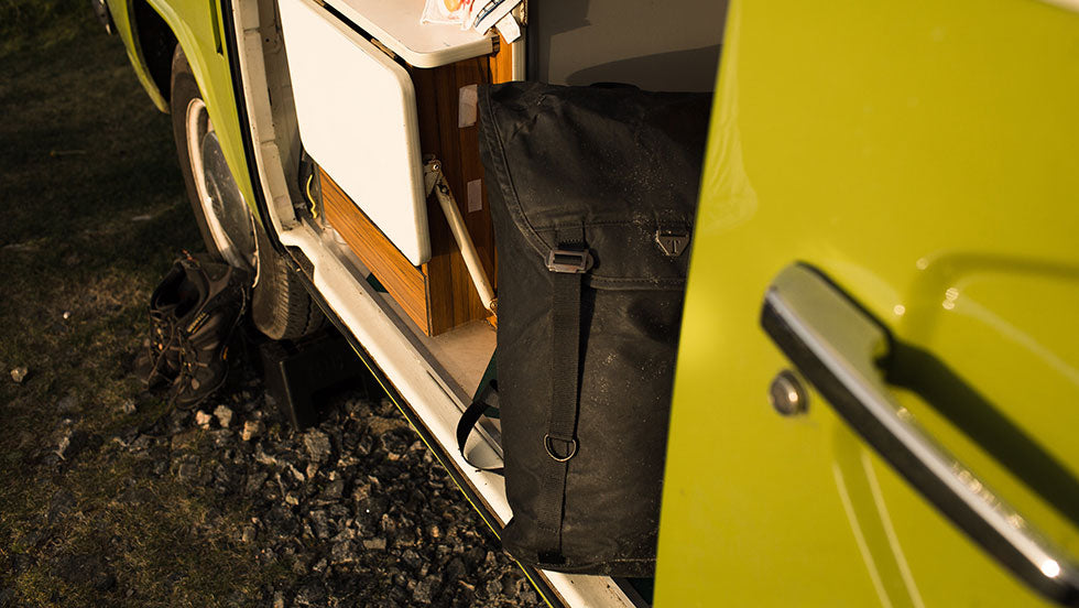 A black Assynt 28 backpack by Trakke sits inside of a VW van in the Outer Hebrides