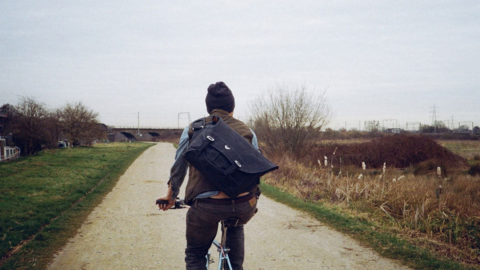 Tim of Isambard's Cycles wearing his Wee Lug waxed canvas messenger bag cycles into the distance