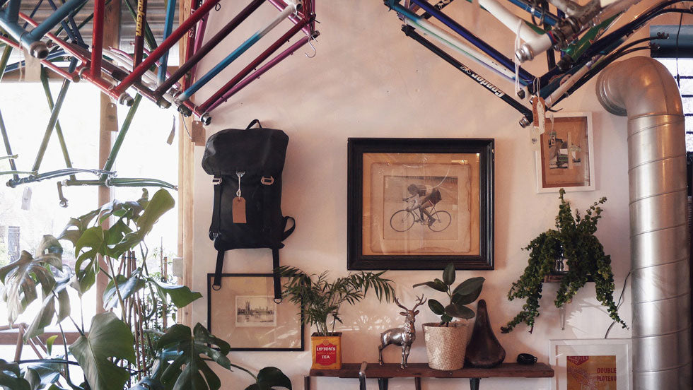 The inside of Isambard's Cycles showing a variety of bike frames hanging from the ceiling, cycling memorabilia on the wall and a Trakke waxed canvas bag