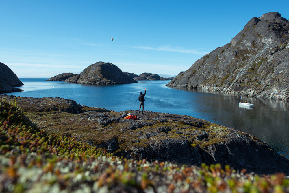 A man stands near a fjord and waves to a passing boat as he controls a drone flying over his head