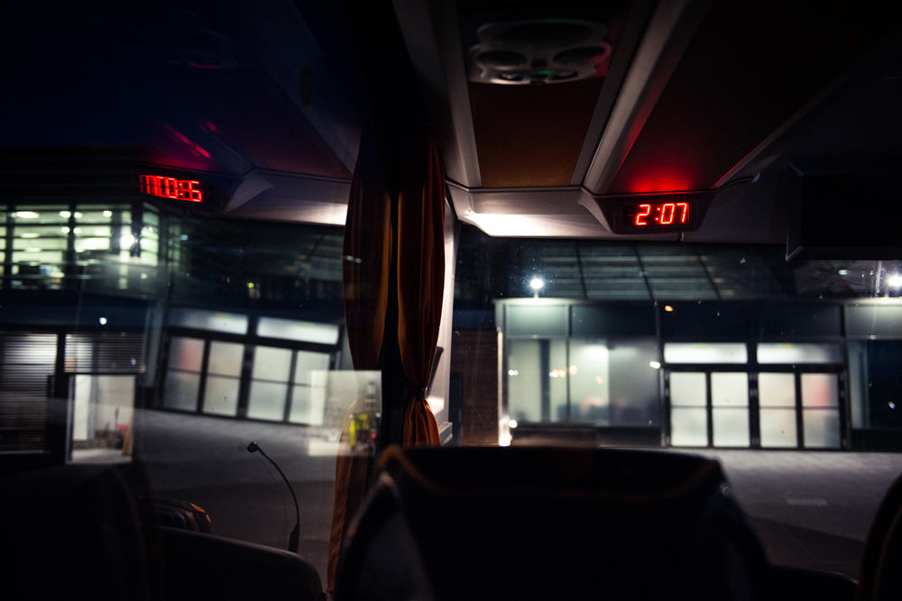 Bus interior looking toward the windscreen, the dashboard clock reads 2:07 as the CALVE research teams continues the journey to Greenland