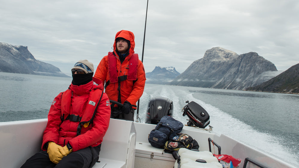 Two members of the CALVE expedition team sit in a speed boat, bundled tightly against the cold. The waterproof Assynt 17 sits on the back bench, unaffected by the spray kicked up by the boat.