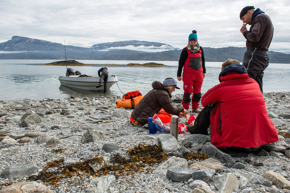 Members of the CALVE expedition team break for lunch on the shore of an fjord in Greenland