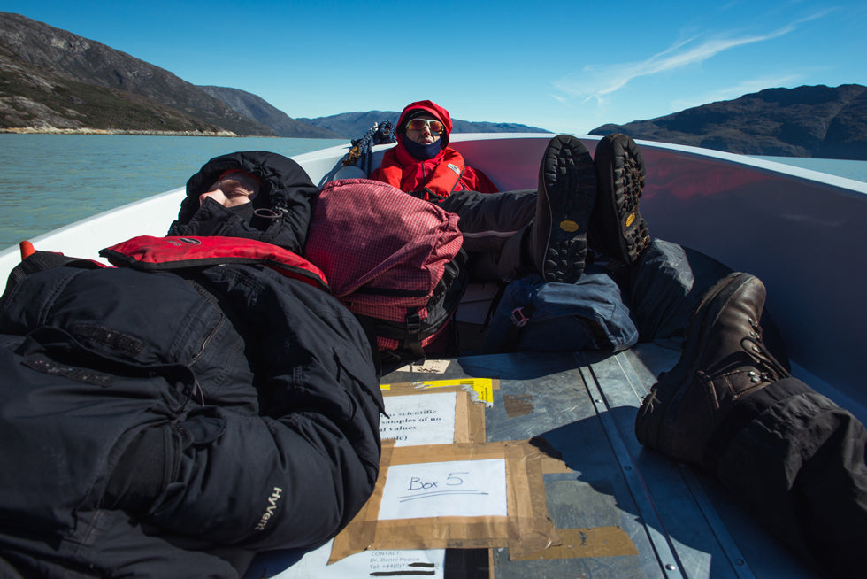 The CALVE research team rests in the sunny boat, bundled against the cold, resting heads and feet against their packs during the Greenland expedition.