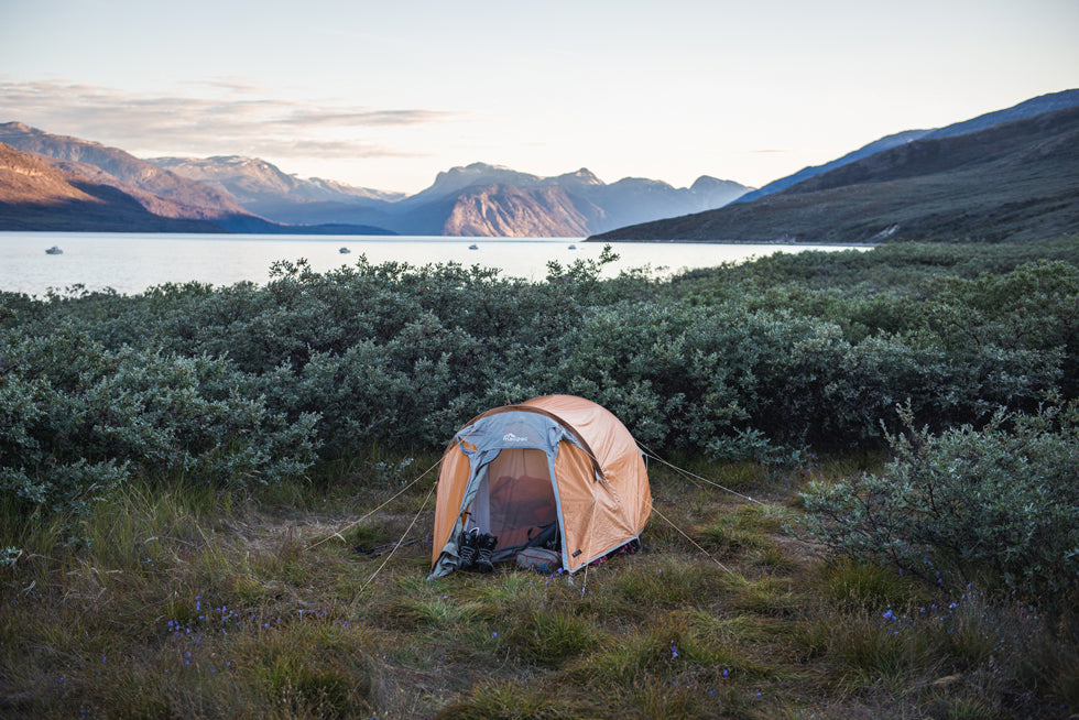 A tent pitched on moorland in front of bushes with a fjord and mountains in the background during the Greenland Expedition