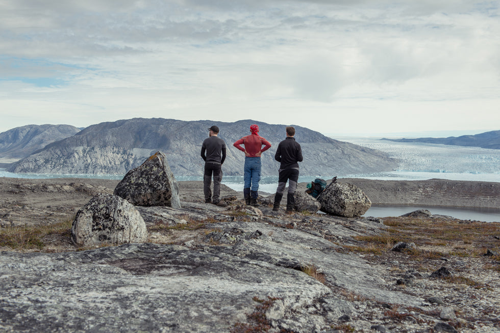 Three hikers rest in a sunny valley while on the CALVE research project during an expedition in Greenland