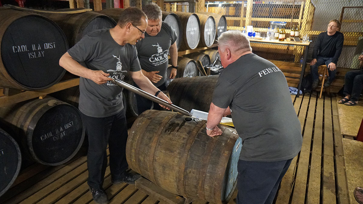 Distillery workers tasting a newly opened cask at Bruichladdich whisky festival