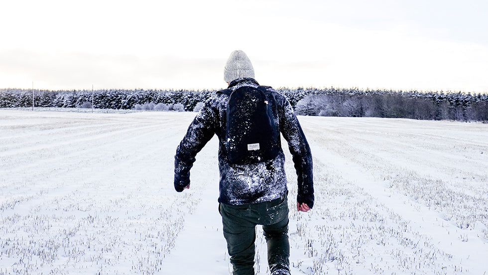 a man walking in the snow with a trakke fingal backpack in black.