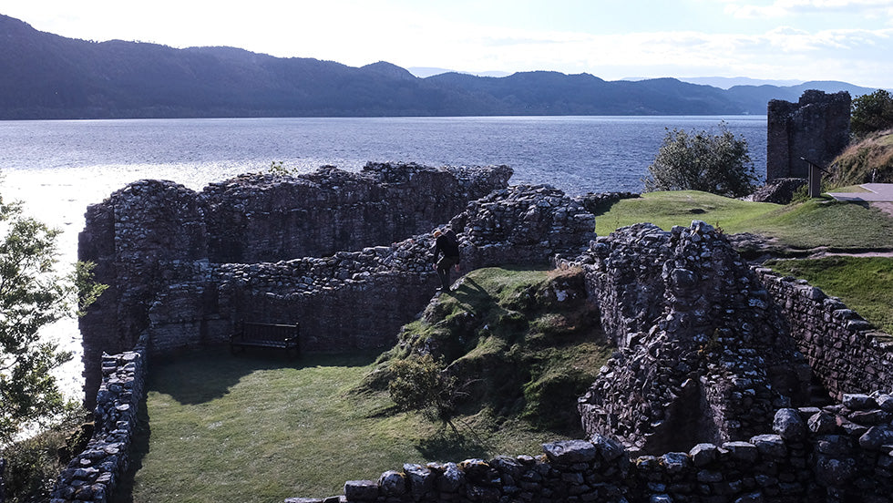 A man explores the ruins of Urquhart Castle