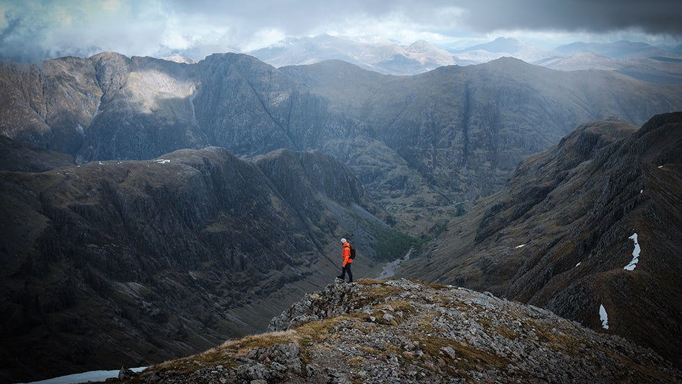 A man in an orange jacket stands at the summit of the Three Sisters in Glencoe