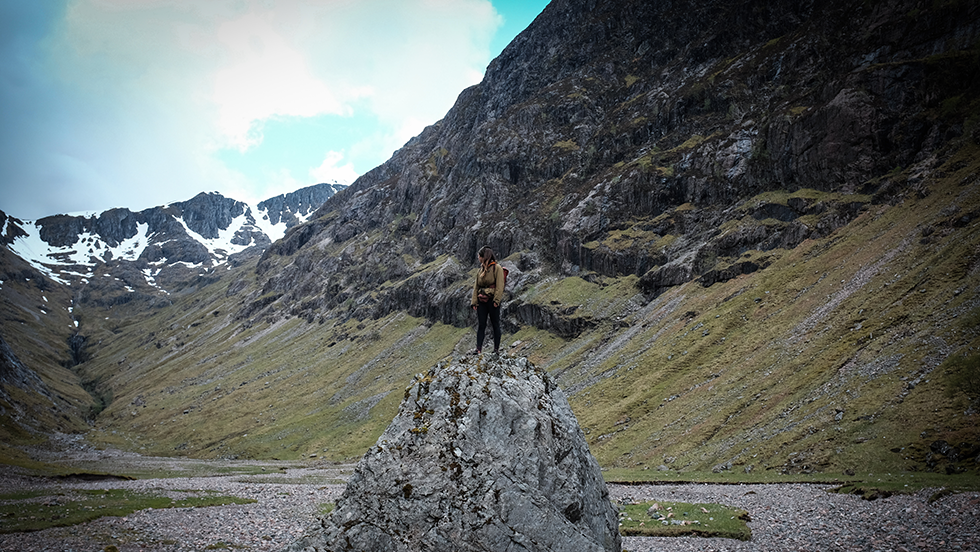 A woman stands on a perch looking at the scottish mountains behind her