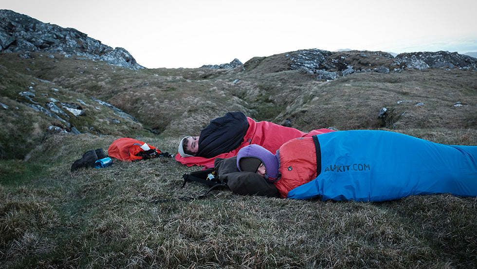 A women and man awake early on a mountain in their bivvy bags