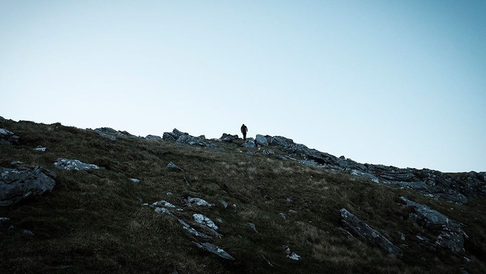 A man climbing to the ridge line to possibly go and take a shit