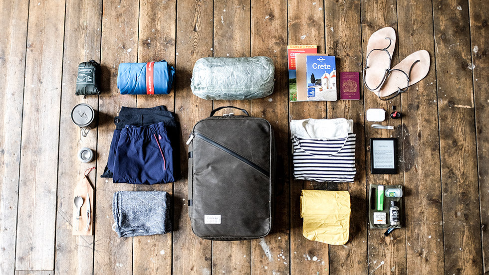 The Storr carry on hand luggage backpack with various pieces of holiday clothing and equipment scattered around