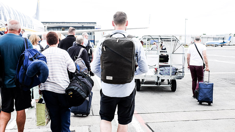 A man wearing his Storr carry on handluggage stands infront of a que of people waiting to board an airplane