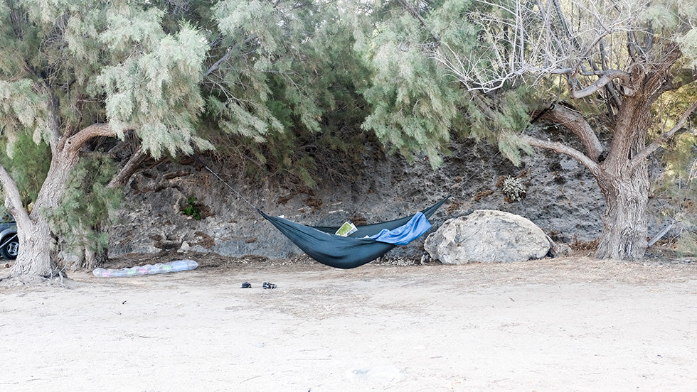 A hammock set up on a beach in Greece