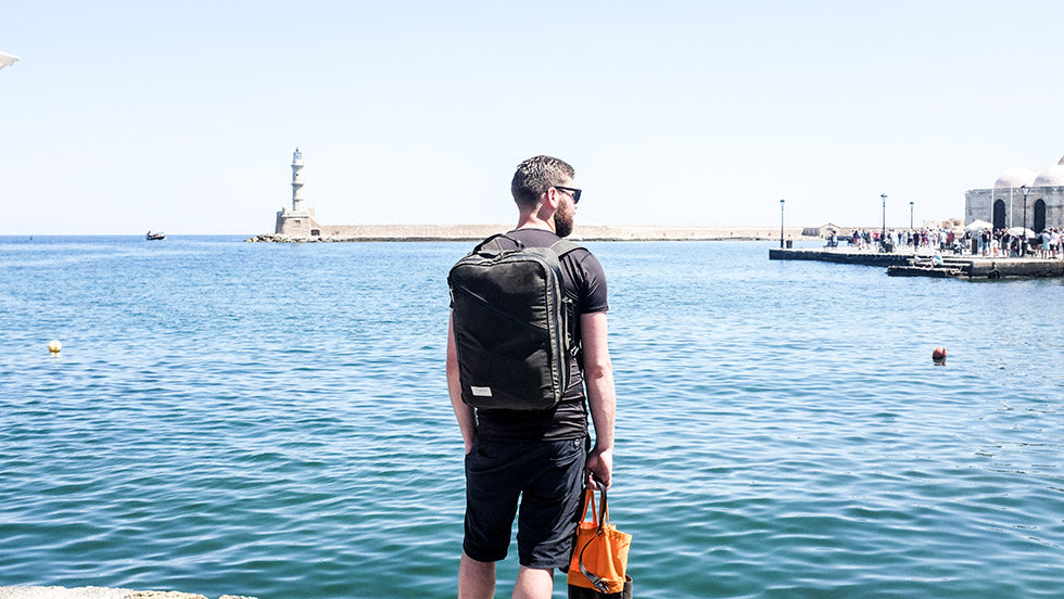 a man stands staring out at the Greek sea with his Storr Carry on Backpack