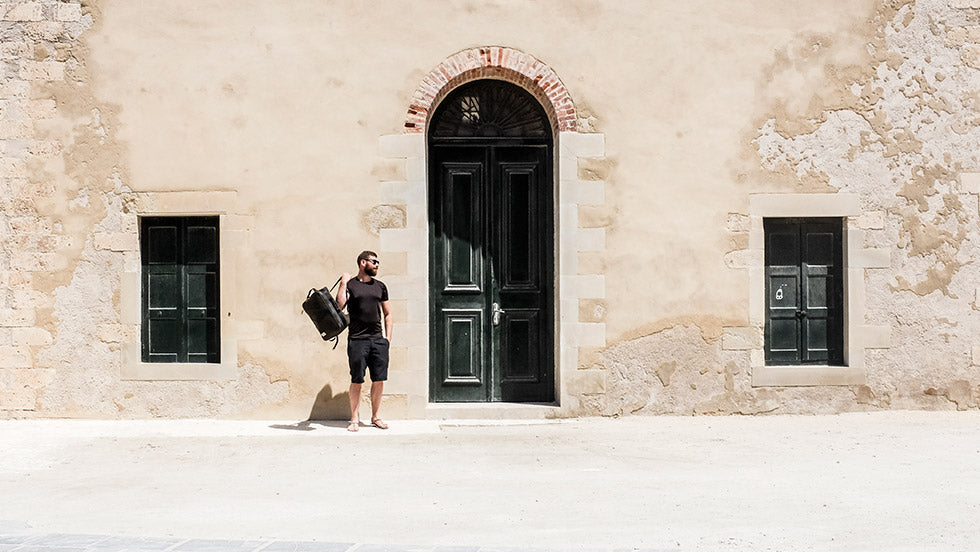 A man and his Storr carry on handluggage backpack stands infront of a sandstone building in Greece