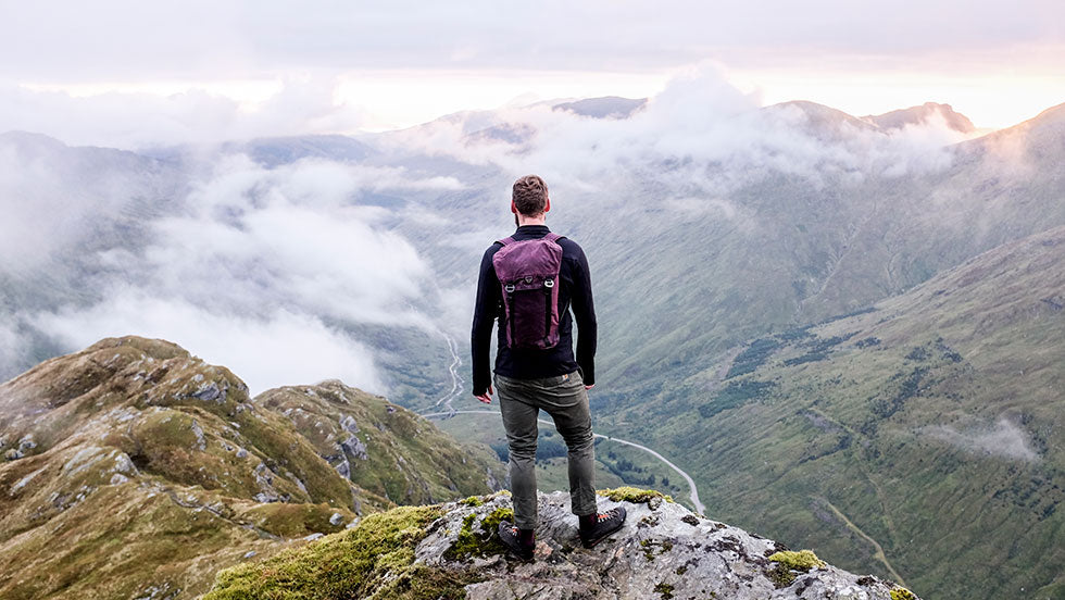 A man wearing a Trakke Assynt 28 backpack stands on top of a mountain called Beinn an Lochan in Scotland.